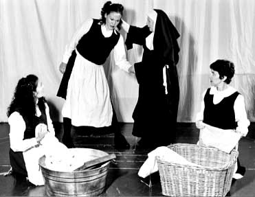 The head nun grabs the hair of one of the Magdalene women, while two other women in the foreground fold laundry. Photo by Adam Liberman.